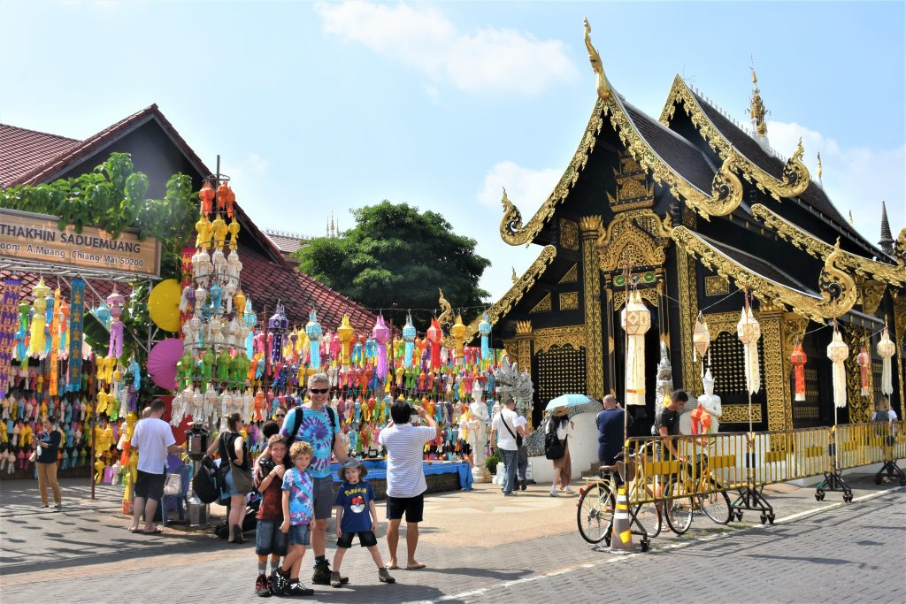 a picture of a family standing outside a temple in chiang mai