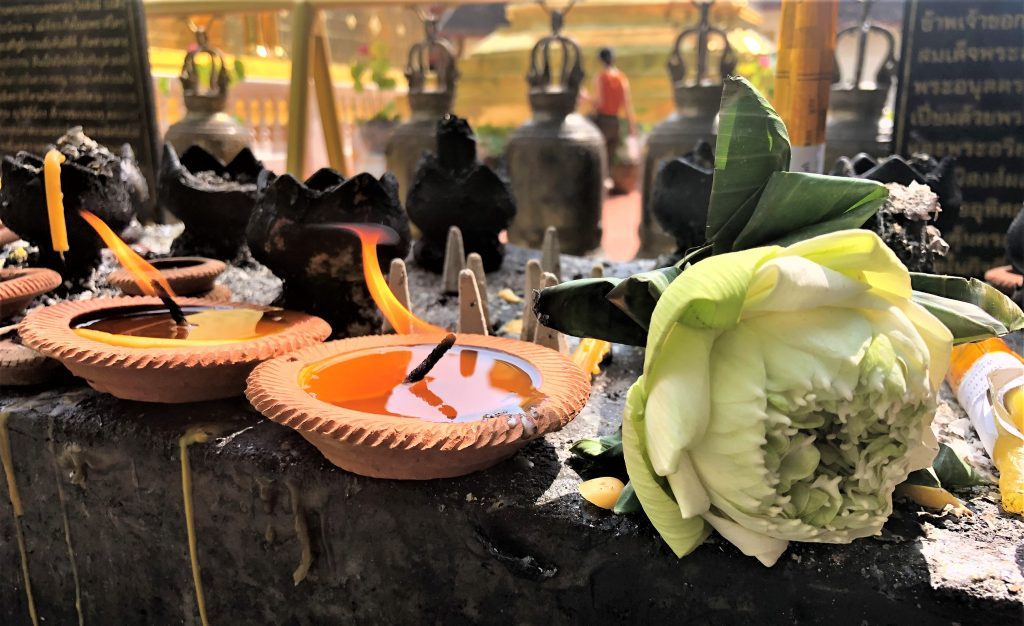 a picture of candles burning and lotus flowers offered at a temple in chiang mai thailand